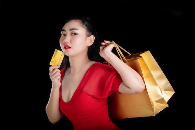 クレジットカードと買い物袋を保持している赤いドレスを着て美しい若いアジアの女性の肖像画