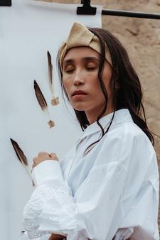 羽と白い紙に白を身に着けている美しい若いアジアの夢のような女性の肖像画。