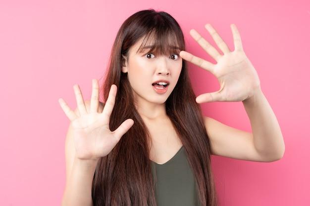 ピンクの壁にポーズをとって美しい若いアジアの女の子の肖像画