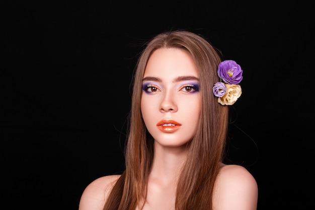 Портрет красивая молодая блондинка с цветами в волосах на черном