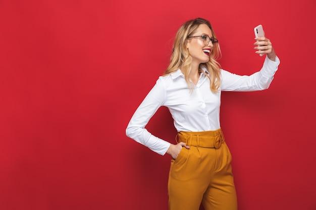 赤い背景の上に孤立して立っている美しい若いブロンドの女性の肖像画、selfieを取る