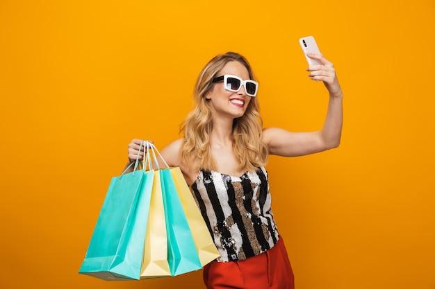黄色の背景の上に孤立して立っている美しい若いブロンドの女性の肖像画、selfieを取る