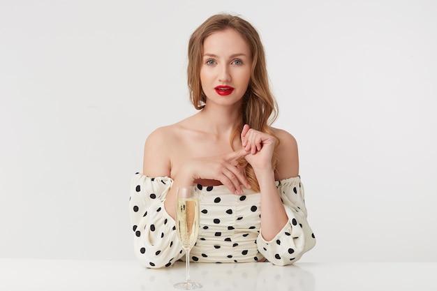 水玉模様のドレスを着た赤い唇を持つ美しい若い青い目のブロンドの肖像画。シャンパングラスを片手にテーブルに座ります。白い背景の上に分離。
