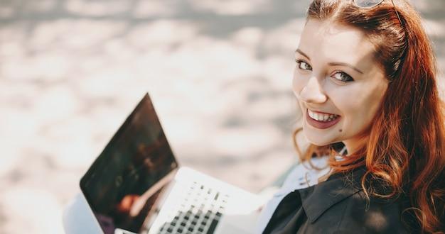 Портрет красивой молодой позитивной женщины, работающей на своем ноутбуке, глядя на камеру, улыбаясь, сидя в парке на скамейке.