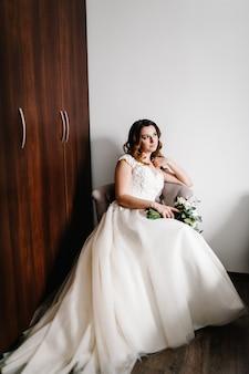 복고풍 안락의 자에 꽃의 웨딩 부케와 드레스에 아름 다운 젊은 신부 초상화. 얼굴에 부드러운 행복한 감정.