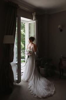 ブライダル ヘアスタイルと豪華なビンテージ インテリアのバルコニーでポーズをとる豪華なウェディング ドレスの花束を持つ美しい若い花嫁の肖像画