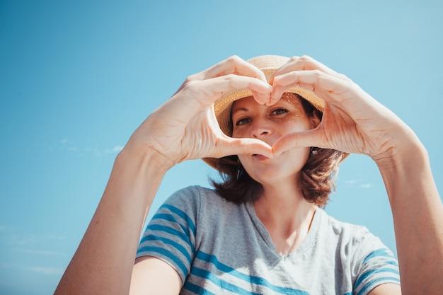 晴れた日の青い空を背景に麦わら帽子をかぶった美しい若いブルネットの女性の肖像リラクゼーション幸せと健康的なライフスタイルの概念