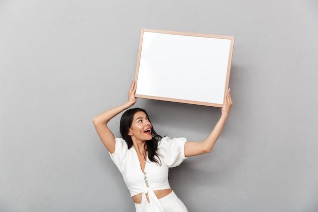 灰色の壁の上に孤立して立っている夏の服を着て、空白のボードを示す美しい若いブルネットの女性の肖像画