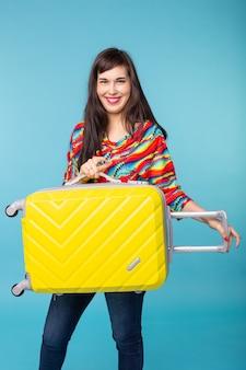 青い表面でポーズをとって彼女の手に黄色のスーツケースを持つ美しい若いブルネットの女性の肖像画。旅行と観光のコンセプト。