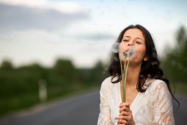 田舎のアスファルト道路にタンポポの花を持つ美しい若いブルネットの女性の肖像画