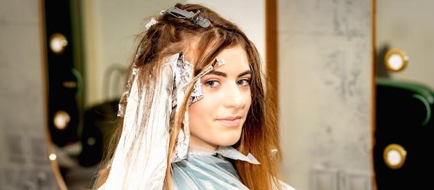 Портрет красивой молодой кавказской женщины, получающей фольгу на волосах перед покраской в салоне красоты