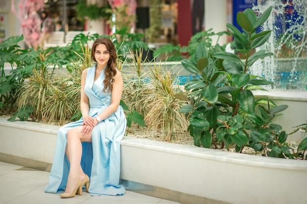 Портрет красивой молодой кавказской женщины, сидящей в цветочном саду на открытом воздухе