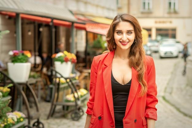 屋外でカメラを見て街の通りに笑顔で立っている美しい若い白人女性の肖像画