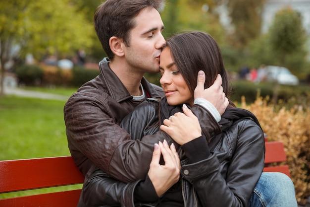 ベンチで屋外で抱き締める美しい若いカップルの肖像画
