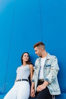青い壁とコピースペースで手をつないで愛の美しい若いカップルの肖像画
