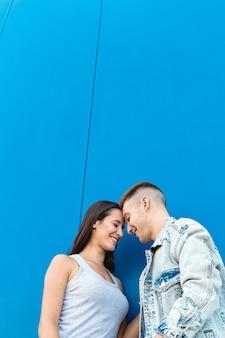 青い壁とコピースペースで笑顔の愛の美しい若いカップルの肖像画
