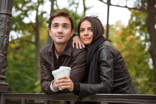 屋外でコーヒーを飲みながら立っている美しい若いカップルの肖像画
