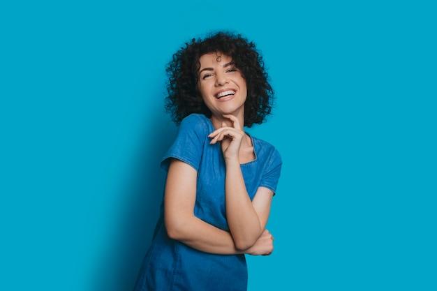 彼女の顔に触れている青いスタジオの壁に分離されたカメラを見ながら笑っているブルージーンズのドレスを着た美しい若い巻き毛の女性の肖像画。