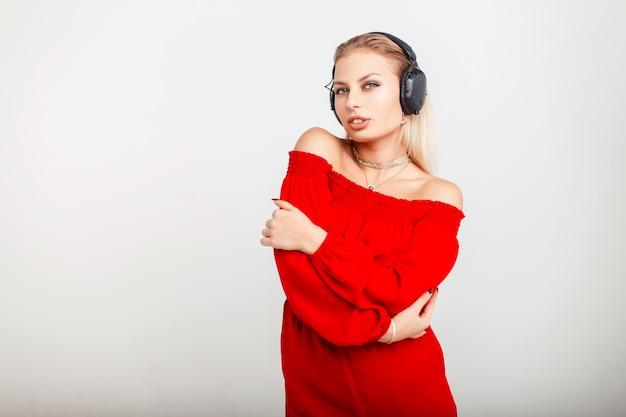 Портрет красивой молодой девушки ди-джея с наушниками в красном платье, слушающей музыку на сером