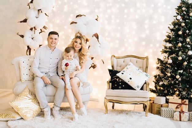 クリスマスツリーを背景に美しい若い家族の肖像画。魅力的な家族が新年と笑顔を祝う