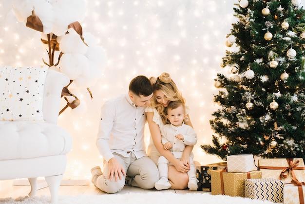크리스마스 트리를 배경으로 아름 다운 젊은 가족의 초상화. 매력적인 부모와 작은 아들은 새해를 축하하고 미소