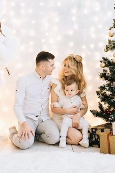 크리스마스 트리에 대 한 아름 다운 젊은 가족의 초상화. 매력적인 부모와 작은 아들은 새해를 축하하고 미소