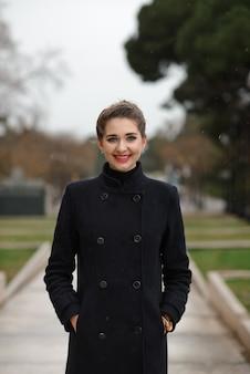 雨の中に黒いコートを着た美しい少女の肖像画。