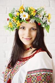 Портрет красивой молодой девушки в украинском национальном костюме и венке из цветов