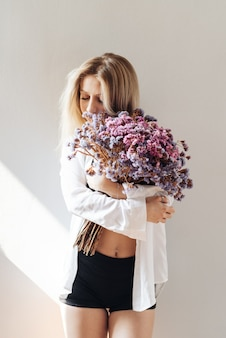 灰色のドライフラワーの大きな花束を保持している白いシャツ、黒のトップとショートパンツの美しい少女の肖像画