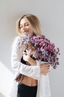 회색에 말린 꽃의 큰 꽃다발을 들고 흰 셔츠, 검은 탑과 반바지에 아름 다운 젊은 여자의 초상화