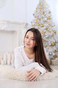 크리스마스 트리 배경에서 아름 다운 젊은 여자의 초상화