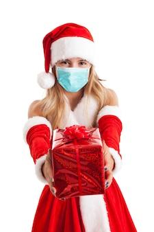 Портрет красивой молодой девушки в рождественском платье в маске из-за пандемии коронавируса