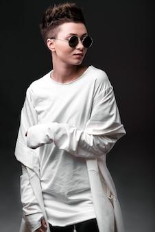 Портрет красивой молодой девушки в белом пальто и солнцезащитные очки