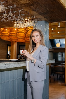 美しいモダンなカフェでおいしいコーヒーを飲む美しい少女の肖像画。