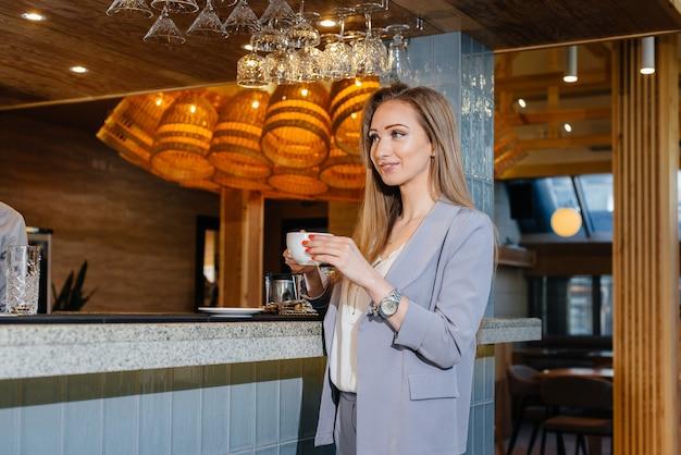 Портрет красивой молодой девушки, пьющей вкусный кофе в красивом современном кафе