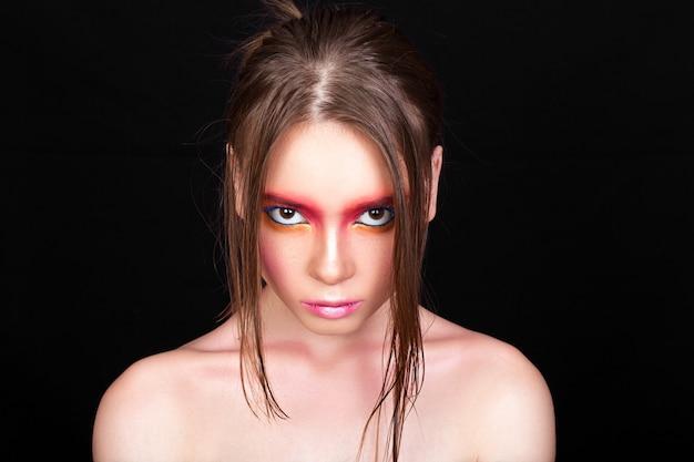 Портрет красивой молодой девушки с творческим макияжем на черном