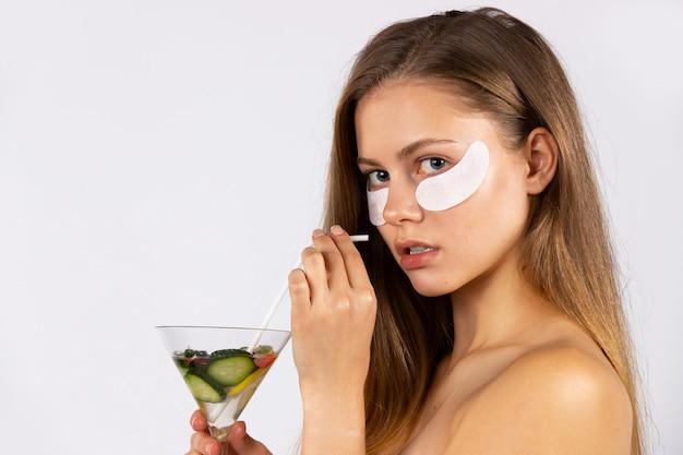 Портрет красивой молодой девушки с длинными волосами под глазами, с повязками на глазах и коктейлем в руках. уход за кожей и концепция здорового питания. фото на белой стене. фото высокого качества