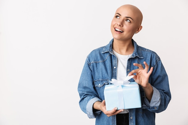 캐주얼 옷을 입고 고립 된 서, 선물 상자를 보여주는 아름 다운 젊은 대머리 여자의 초상화