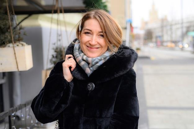 街の通りを歩いているファッショナブルな冬の毛皮のコートで美しい若い幸せな女性の肖像画