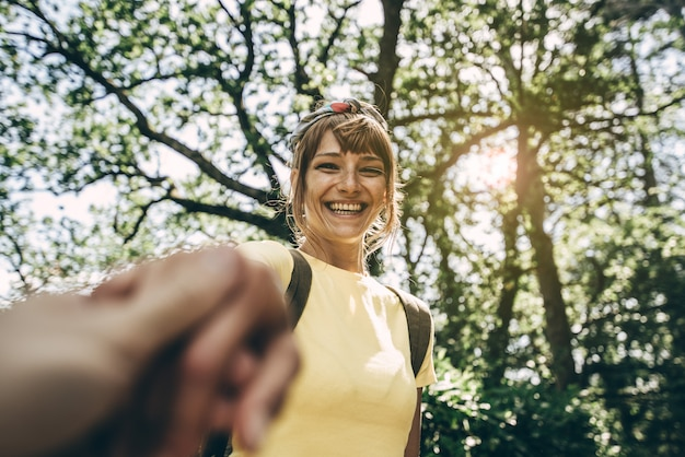 バックパックの手を握って、見て笑みを浮かべて美しい若いハイカー女性の肖像画。ハメ撮りビュー。