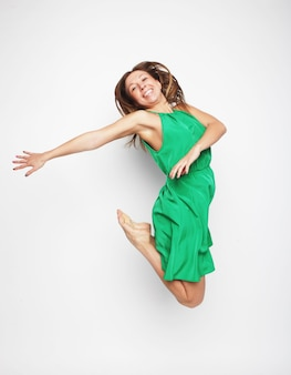 Портрет красивой молодой леди, прыгающей от радости на белом фоне