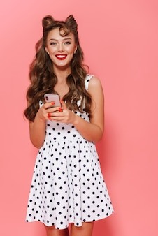 Портрет красивой молодой девушки пин ап в платье стоя изолированно, держа мобильный телефон