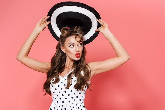 Портрет красивой молодой девушки пин ап в платье стоя изолированно, позирует, держа пляжную шляпу