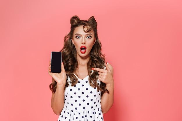 Портрет красивой молодой девушки пин ап в платье, стоящем изолированно, показывая пустой экран мобильного телефона