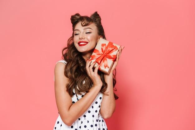 Портрет красивой молодой девушки пин ап в платье, стоящем изолированно, показывая подарочную коробку