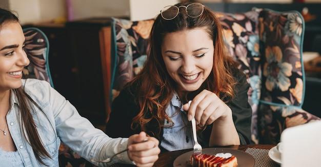커피 숍에서 그녀의 여자 친구와 치즈 케일을 먹는 동안 눈을 감고 웃고있는 아름다운 젊은 더하기 크기 여성의 초상화.