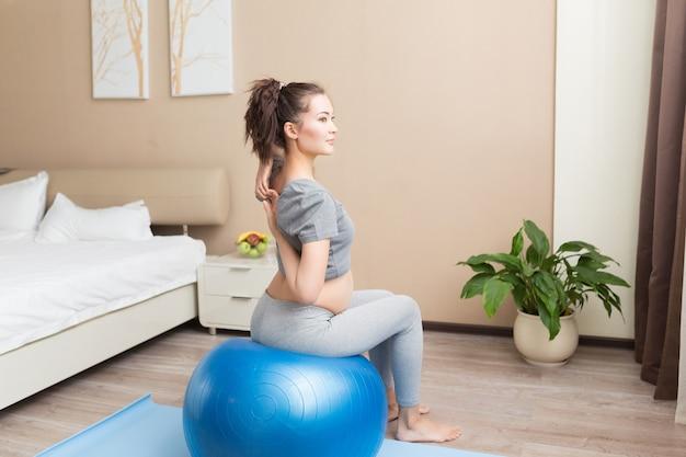 美しい若い妊婦の肖像画は、国内の部屋で青いフィットボールでエクササイズします。ワークアウトとフィットネス、妊娠の概念。