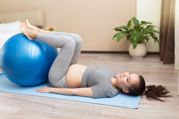 国内の部屋で青いfitballとエクササイズ美しい若い妊婦の肖像画