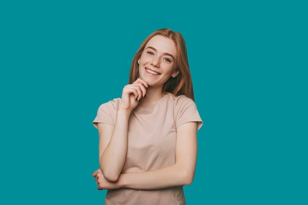 青いスタジオの壁に手で彼女の顔に触れながら笑顔のカメラを見てそばかすのある美しい若い赤い髪の女性の肖像画。