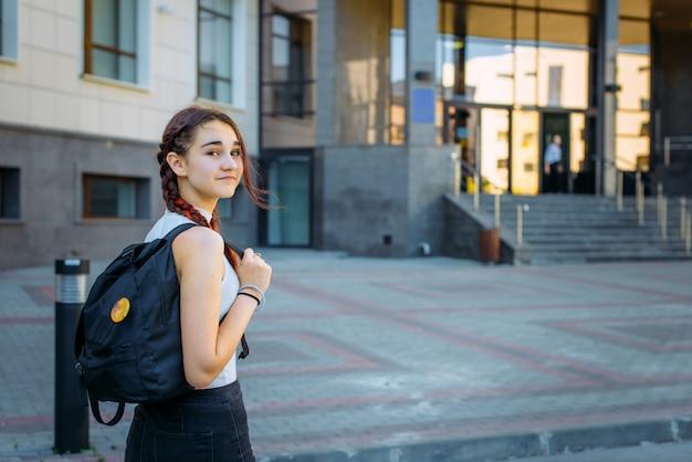 Портрет красивой молодой школьницы с рюкзаком и длинными косами